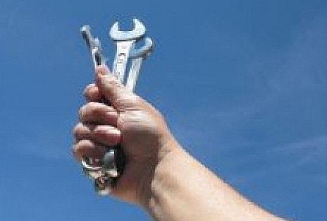 narzędzia trzymane w dłoni podniesione do góry na niebieskim tle