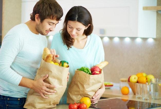 małżeństwo i torby pełne warzyw i owoców